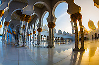 Sunset sunrays over the Sheikh Zayed Grand Mosque with beautiful minarets and columns reflecting on the marble floor, in Abu Dhabi, Asia (fisheye)
