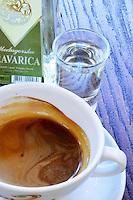 Triangular pyramid shaped Bottle of Travarica rakija grappa type grape spirit, a cup of espresso coffee and a glass of digestif alcohol. In the restaurant and wine bar at the winery. Podrum Vinoteka Sivric winery, Citluk, near Mostar. Federation Bosne i Hercegovine. Bosnia Herzegovina, Europe.