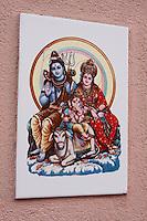 Kathmandu, Nepal.  Hindu Religious Plaque by Doorway Shows Shiva, Parvati, and their Son, Ganesh.