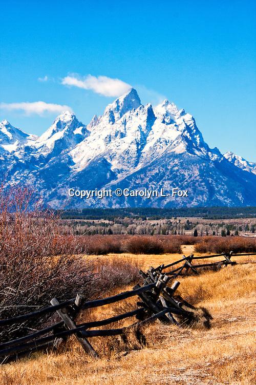 A split rail fence leads to the Teton Mountain Range in Wyoming.