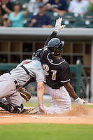 Jared Mitchell (21) of the Charlotte Knights slides across home plate for an inside-the-park home run against the Pawtucket Red Sox at BB&T Ballpark on August 9, 2014 in Charlotte, North Carolina.  The Red Sox defeated the Knights  5-2.  (Brian Westerholt/Four Seam Images)
