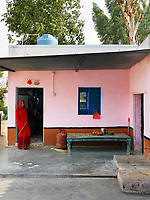 Pintu Panday stands in the doorway to her kitchen. The low table in the courtyard is used as seating and also serves as an extra worktop.  To the far right is a tap for washing large pots