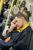 A young man sleeps on the London underground