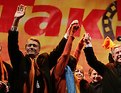 """Kiev, Ukraine.December 26, 2004..Opposition candidate Viktor Yushchenko takes center stage on Maidan Independence Square as thousands of Orange flag waving supporters rally to his side. Election polls show him in a strong lead just hours after the polling stations close. ..He is joined on stage by his wife Kathy, his son Andrey and his political partner Yulia Timoshenko. Holding his hand to the right is Ruslana, the famous Ukrainian singer who won the 2004 Eurovision song contest...The first round of voting was considered fraudulent when the ruling president Viktor Yahukovich won and the opposition candidate Viktor Yushchenko lost. ..Several hundred thousand Ukrainians took to the streets of Kiev and held daily rallies on Maidan Independence Square. The protests lasted nearly a month before the first vote was declared invalid and a new round of elections held on December 26, 2004. ..The demonstrations would come to be known as the """"Orange Revolution"""" after the color of the opposition party."""