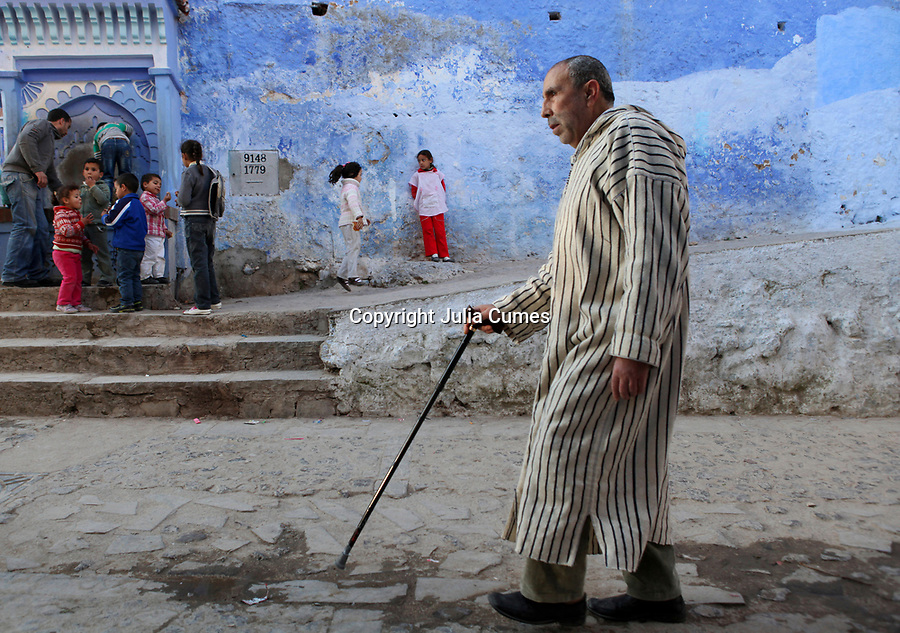 "A blind man walks past one of the public drinking fountains where children are gathered in Chefchaouen, Morocco, whose ""medina"" (old city) is famous for its striking blue walls."