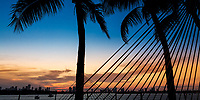 Colorful sunset on Miami's Biscayne Bay with palm tree and hammock rope silhouettes in the foreground, from Miami Beach Art Deco district, Florida USA