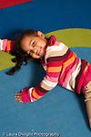 Preschool 3-5 year olds portrait of girl lying on floor looking up vertical