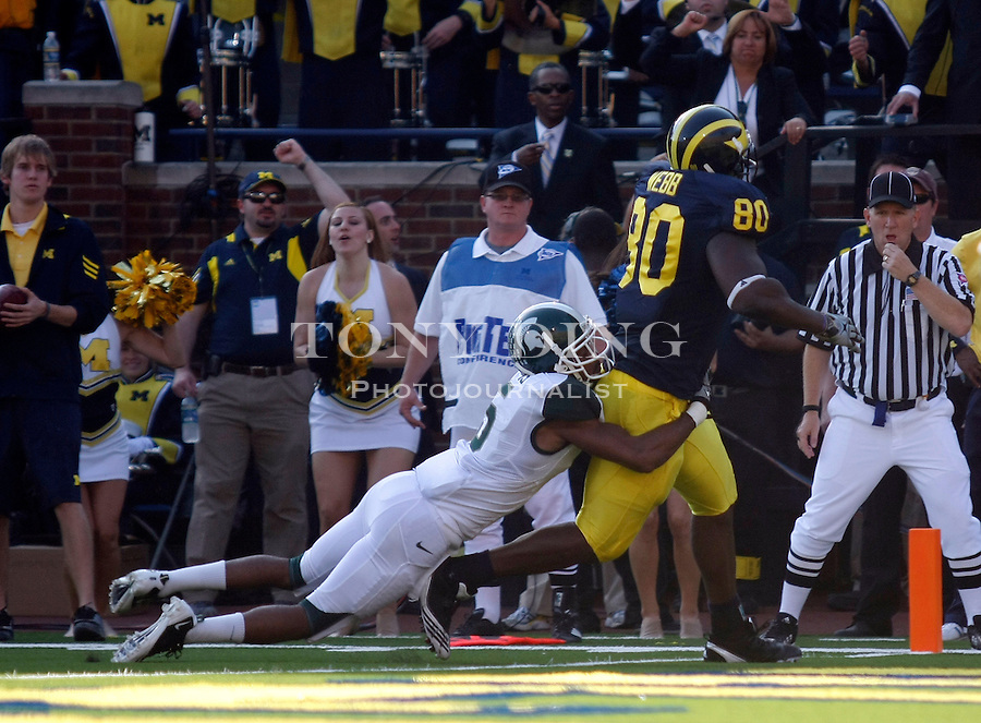 Michigan State cornerback Johnny Adams (5) hangs on to Michigan tight end Martell Webb (80) rushing for a touchdown in the second quarter of an NCAA college football game, Saturday, Oct. 9, 2010, in Ann Arbor, Mich. (AP Photo/Tony Ding)