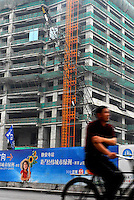 Residents pass an advertisement for a new office complex under construction in Shanghai, China..14 June 2006