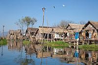 Myanmar, Burma.  Village Houses on Stilts along Waterway, Inle Lake, Shan State.