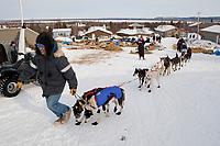 Volunteer in Shageluk helps Bob Bundtzen maneuver his dogs out of the Shageluk checkpoint during Iditarod 2009