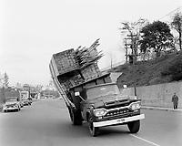 Chargement de planches de bois sur une camionette Mercury, dangereusement inclinée, date inconnue