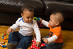Sitting 5 month old baby boy shaking plastic chain and knocking it against shoulder of cousin, boy 12 months old
