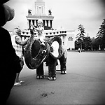 A little girl mounted on an elephant to pose for a picture, with the Central  (former USSR) pavilion at the background. Moscow, Russia, 2009