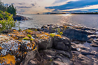 Sunrise light and storm clouds and lichen-covered bloulders on the shore of Lake Superior in Rock Harbor; Isle Royale National Park, MI