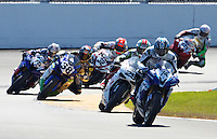 A pack of motorcycles races through a turn during the Daytona 200 motorcycle race at Daytona International Speedway, Daytona Beach, FL, March 2011.(Photo by Brian Cleary/www.bcpix.com)