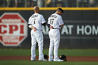 (L-R) Charlotte Knights shortstop Ryan Goins (1) and second baseman Danny Mendick (17) stand for the National Anthem prior to the game against the Gwinnett Braves at BB&T BallPark on July 12, 2019 in Charlotte, North Carolina. The Stripers defeated the Knights 9-3. (Brian Westerholt/Four Seam Images)