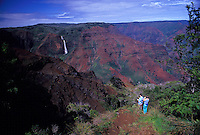 Couple overlooking Waimea Canyon with Waipoo Falls , view from Waimea Canyon Drive, West Kauai.