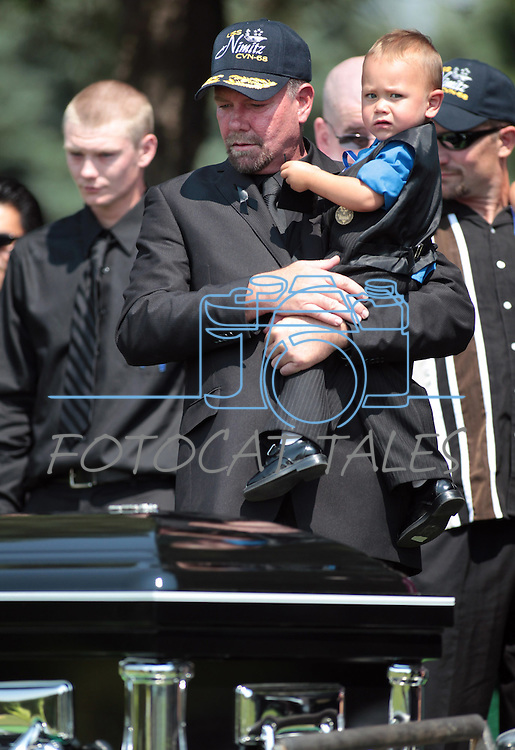 Randy Blunk holds his grandson Maximus, 2, following the graveside service for his son Jonathan Blunk who was killed in the July 20 Colorado movie theater shooting. An estimated 500 people attended the memorial service in Reno, Nev. on Friday morning, Aug. 3, 2012. Blunk's other son Dillon is at left. (AP Photo/Cathleen Allison)