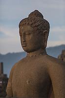 Borobudur, Java, Indonesia.  Buddha Statue Receiving First Rays of the Sun.