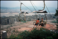 "Fengdu, China, August 2003.Chinese tourists visiting the old city of Fengdu, already half-destroyed to allow the Three Gorges Dam project to be completed. In the background, the ""new"" city on the right bank of the Yangtze Kiang river.."