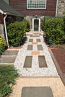 Entrance to house made more appealing with simple stone path and tier of plants and shrubs
