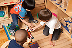 Education Preschool 3-4 year olds group of boys playing with vehicles and blocks