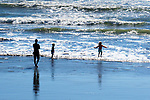 Family, mother and two children, play on beach.  Silhouette, Kalaloch Beach in Olympic National Park, Washington.  Beaches in the Kalaloch area of Olympic National Park, identified by trail numbers, are remote and wild.  Olympic Peninsula, Olympic Mountains, Olympic National Park, Washington State, USA.