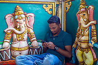 Court Hill Ganesh Temple, Hindu, Kuala Lumpur, Malaysia.  Young Man with Cell Phone beside Ganesh Sculpture.