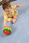 8 month old baby boy sitting full length leaning over to reach colorful plastic ball