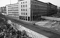 """DEUTSCHLAND, 11.1989.Berlin - Mitte.Fall der Berliner Mauer: Blick ueber die geteilte Wilhelmstrasse auf das DDR-""""Haus der Ministerien"""" (zuvor Goerings Reichsluftfahrtministerium, heute das Finanzministerium). Auf dem Mauerstreifen patrouillieren immer noch die DDR-Grenzsoldaten mit ihren MZ-Motorraedern..Fall of the Berlin Wall: View across cut-off Wilhelmstrasse onto the GDR-""""House of Ministries"""" (before Goring's Imperial Aviation Ministry, today Ministry of Finance). The wall is still patrolled by GDR border troops on their MZ motorbikes..© Martin Fejer/EST&OST"""