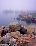 Mystic, CT<br /> Morning fog envelops a fishing dock and boulders on the shoreline of Mystic harbor in the village of Noank