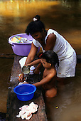 Amazon, Brazil. Caboclo woman washing the clothes in the river on a log with her daughter. Amapa State.