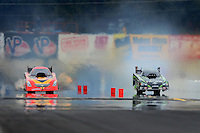Oct. 7, 2012; Mohnton, PA, USA: NHRA funny car driver Alexis DeJoria (right) yanks the front end off the ground in a pedal fest in a losing effort alongside Jim Head during the Auto Plus Nationals at Maple Grove Raceway. Mandatory Credit: Mark J. Rebilas-