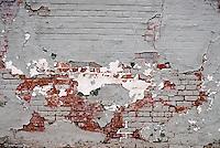 Peeling paint exposing brick wall<br />