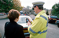 Traffic police officer breathalysing a motorist. The officer is using a handheld Lion Alcometer breathalyser called an SL2. This image may only be used to portray the subject in a positive manner..©shoutpictures.com..john@shoutpictures.com