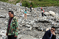 Tourists scramble over moraine (glacially deposited rocks and stones) on the surface of the Hailuogou glacier in western Sichuan Province, China. As a result of rising temperatures on the Tibetan Plateau, the Hailuogou glacier has retreated over 2 km during the 20th century alone. Since the Little Ice Age, studies have revealed that the total monsoonal glacier coverage in the southeast of the Tibetan Plateau has decreased by as much as 30 percent, causing alarm in scientific circles.