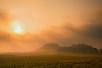 Rays from a setting sun break through fog and clouds onto a green pasture in Waiki'i Ranch, Kamuela, Big Island.