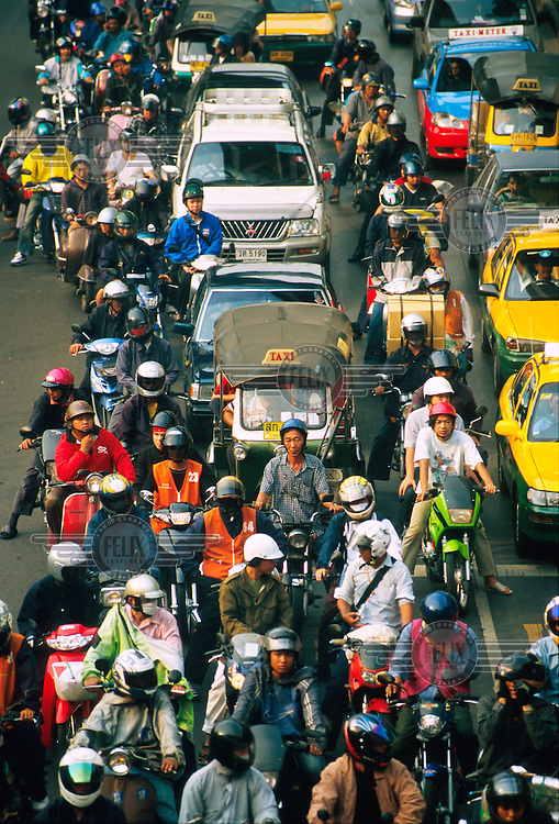 Motorcycles and cars stuck in a traffic jam.