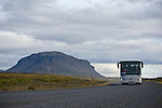 The tour bus travels along a typical dirt road found in Iceland while headed for the Blue Lagoon.