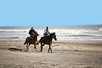 Two men ride horses at Rosarito, Baja California, Mexico