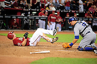 Jul 20, 2008; Phoenix, AZ, USA; Arizona Diamondbacks base runner Stephen Drew lays down after being tagged out at home plate by Los Angeles Dodgers catcher Russell Martin after trying to score an in the park home run in the fourth inning at Chase Field. Mandatory Credit: Mark J. Rebilas-