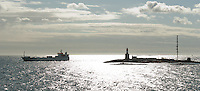 Harmaja Lighthouse and Pilot Station in silhouette with a passing ship in the Gulf of Finland south of Helsinki.
