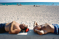 """Spain. Mallorca in the Balearic islands. Palma. Two men, both tourists , take a rest, sunbathe and sleep, stripped to the waist, on a concrete wall in the sandy beach of """" Playa de Palma"""". © 1999 Didier Ruef"""