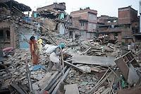 Nepali people carry their belongings through  collapsed houses at Vaktapur, outskirt of Kathmandu, Nepal. May 1, 2015