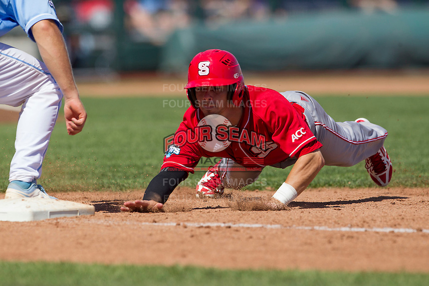 North Carolina State first baseman Tarran Senay (32) dives back to first base during Game 3 of the 2013 Men's College World Series between the North Carolina State Wolfpack and North Carolina Tar Heels at TD Ameritrade Park on June 16, 2013 in Omaha, Nebraska. The Wolfpack defeated the Tar Heels 8-1. (Andrew Woolley/Four Seam Images)
