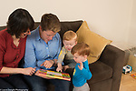 Fraternal twin boys, age 22 months, at home with parents looking at picture books, language development, talking and pointing