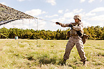 October 22, 2014. Camp LeJeune, North Carolina.<br />  LCpl. Christine Ruperto, age 24, of artillery Battery A of the Ground Combat Element Integrated Task Force, pulls on a tent cord as her unit rushes to camouflage their trucks and howitzers.<br />  The Ground Combat Element Integrated Task Force is a battalion level unit created in an effort to assess Marines in a series of physical and medical tests to establish baseline standards as the Corps analyze the best way to possibly integrate female Marines into combat arms occupational specialities, such as infantry personnel, for which they were previously not eligible. The unit will be comprised of approx. 650 Marines in total, with about 400 of those being volunteers, both male and female. <br />  Jeremy M. Lange for the Wall Street Journal<br /> COED