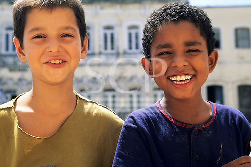 Bahia, Brazil. Two boys, smiling on the street in Pelourinho, one of European descent, the other one, African.