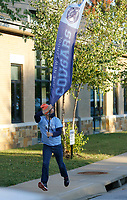 Troy Schremmer, early childhood music teacher at The New School, runs with a banner as he greets students Thursday, October 1, 2020, as they are dropped off at the school for a day of classes in Fayetteville. Check out nwadg.com/photos for a photo gallery.(NWA Democrat-Gazette/David Gottschalk)